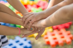 Different children hold their hands together
