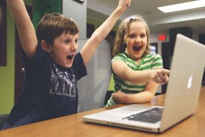 Two happy children behind a laptop