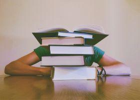 Leerling verscholen achter stapel boeken