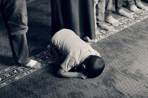 a boy prays while kneeling