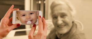 oude vrouw met in de voorgrond een smartphone met foto van een kind