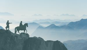 silhouette of a knight on horseback on a mountain