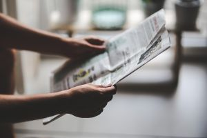 Two hands holding a newspaper
