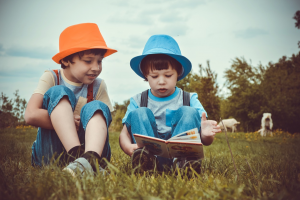 two boys read on the grass in a book